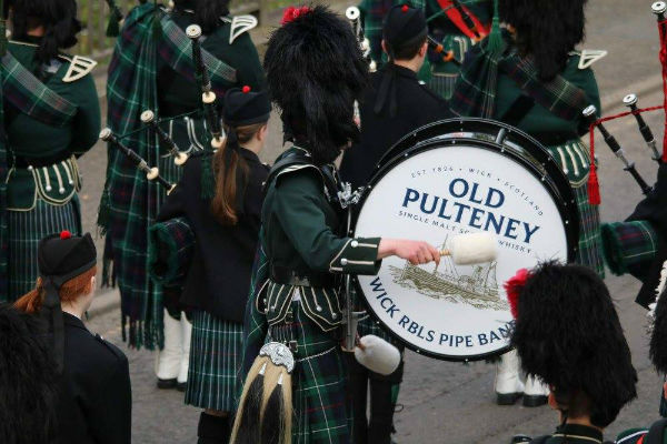 A pipe band playing with Old Pulteney being advertised on the side of a drum