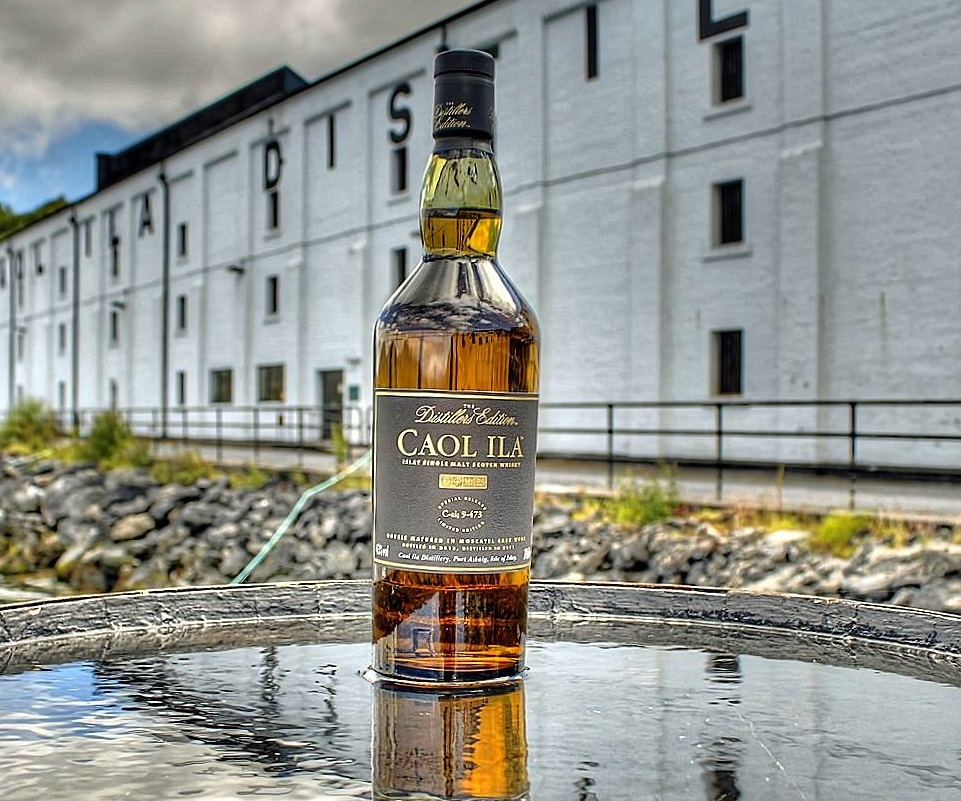 a bottle o Caol Ila whisky sitting outside Caol ila distillery