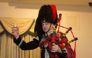 Spud the piper with a whisky in hand